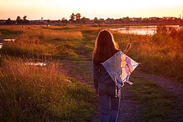 Caucasian teenage girl carrying kite on dirt path