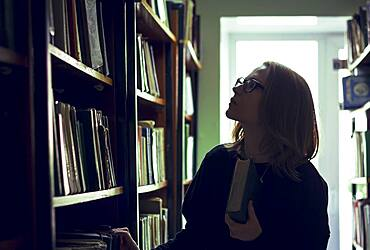 Caucasian woman searching for book in library