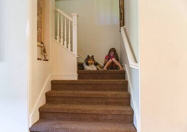 Caucasian girl and dog sitting on stairs