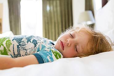 Caucasian boy sleeping on bed