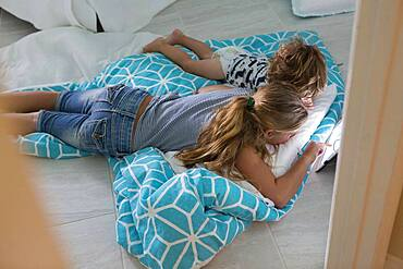 Caucasian brother and sister using digital tablet on bed