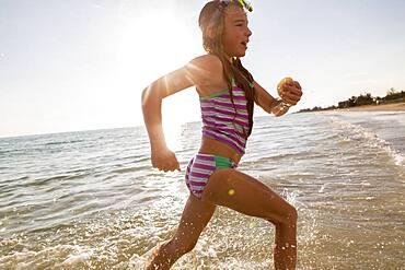 Caucasian girl running in ocean waves on beach