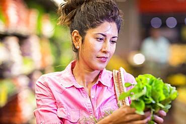 Hispanic woman examining produce at grocery store