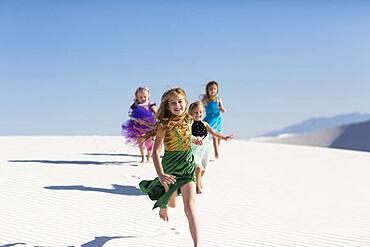 Girls running on desert sand dunes