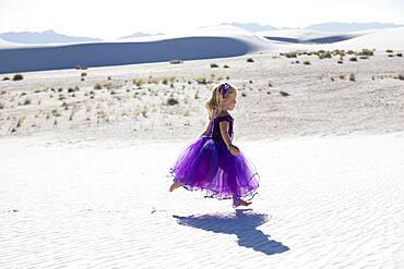 Caucasian girl walking on desert sand dunes