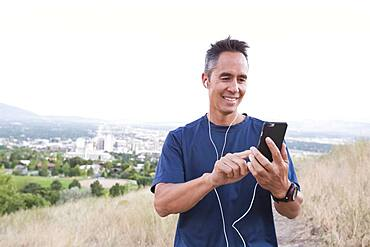 Mixed race man using cell phone on hilltop