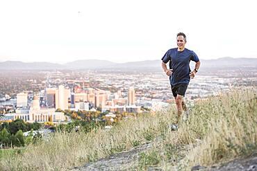 Mixed race man running on hilltop over Salt Lake City, Utah, United States