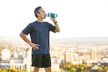 Mixed race man drinking water bottle on urban hilltop