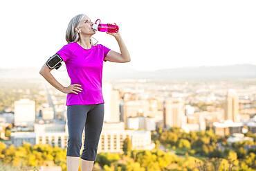 Caucasian woman drinking water bottle on urban hilltop