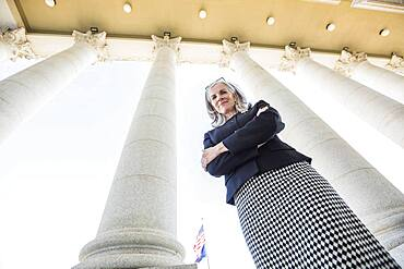 Low angle view of Caucasian businesswoman standing under columns