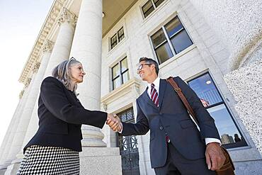 Business people shaking hands courthouse