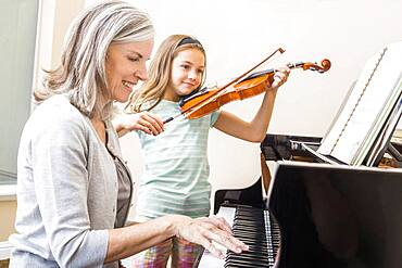 Caucasian grandmother and granddaughter playing music together