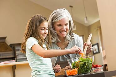 Caucasian grandmother and granddaughter making salad in kitchen