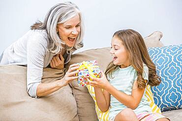 Caucasian girl giving grandmother a gift in living room