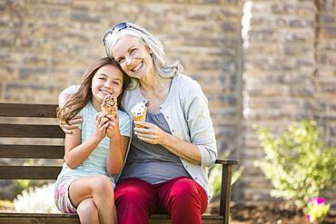 Caucasian grandmother and granddaughter eating ice cream