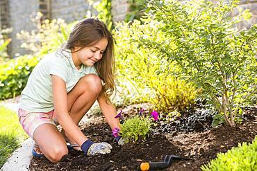 Caucasian girl planting seedling in backyard