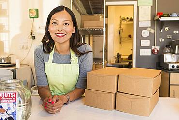 Asian baker smiling in bakery