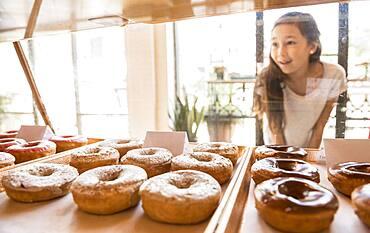 Mixed race girl examining donuts in bakery