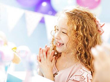 Close up of girl clapping at birthday party