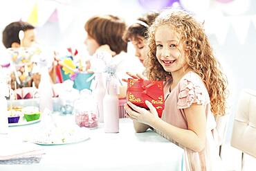 Girl holding wrapped gift at birthday party