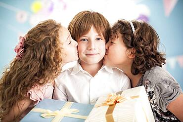 Girls kissing cheeks of boy at birthday party
