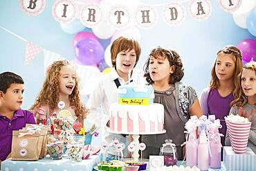 Children blowing out candles on birthday cake at party