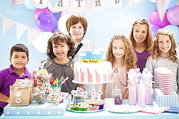 Children smiling near cake and gifts at birthday party