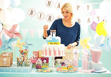Woman lighting candles on birthday cake at party