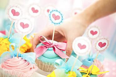 Close up of hand choosing cupcake at birthday party