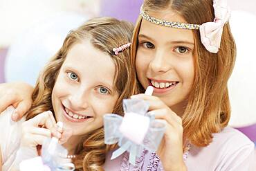 Smiling girls holding noisemakers at party