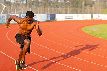 Black athlete running on track in sports field