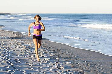 Caucasian woman jogging on beach