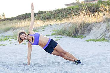 Caucasian woman working out on beach