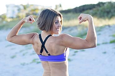 Caucasian woman flexing muscles on beach