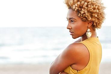 Profile of pensive Black woman at beach