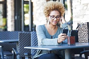Black woman using cell phone at cafe