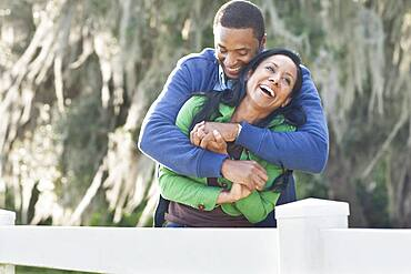 Couple hugging near fence