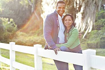 Smiling couple leaning on fence
