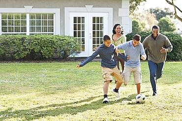 Family playing soccer in backyard