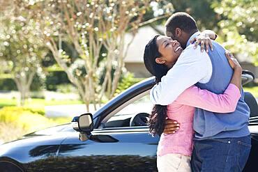 Couple hugging near convertible