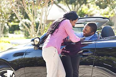 Couple hugging in convertible
