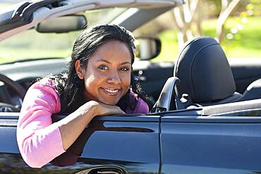 Indian woman smiling in convertible