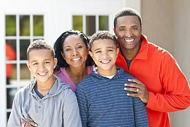 Mother, father and sons smiling outdoors