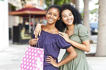Black women smiling on city sidewalk