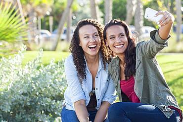 Smiling women taking selfie in park