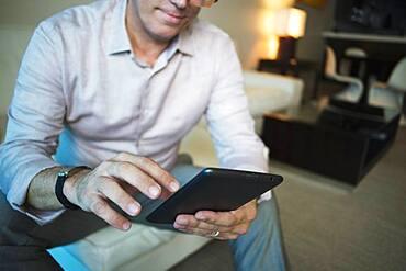 Caucasian businessman using digital tablet in hotel room