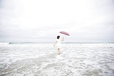Woman wading with umbrella on beach