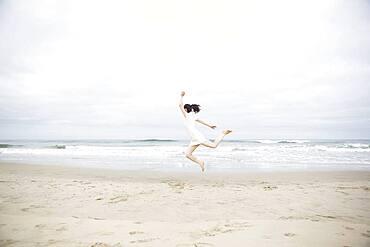 Woman jumping for joy on beach
