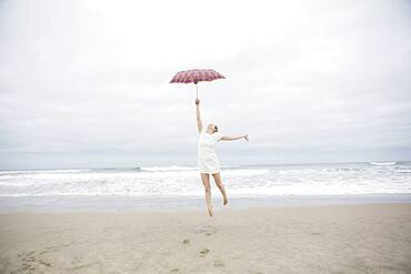 Woman playing with umbrella on beach