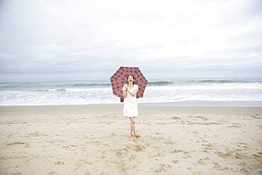 Woman laughing with umbrella on beach